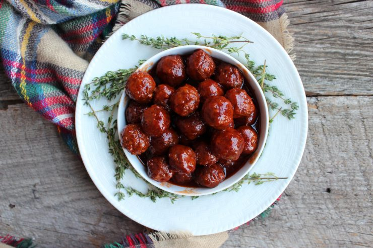 A white bowl filled with Slow Cooker Party Meatballs is sitting on a white plate with fresh sage branches around it. There is a red, blue, green, yellow and tan plaid cloth under the plait and everything is sitting on a wooden backdrop.