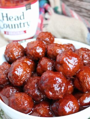 A white bowl filled with Slow Cooker Party Meatballs sits in the foreground on top of a white plate that has fresh sage branches around it. A bottle of Head Country Bar-B-Q Original Sauce is sitting in the background and a plaid cloth is underneath the plate and bottle. Everything is on a wooden backdrop.