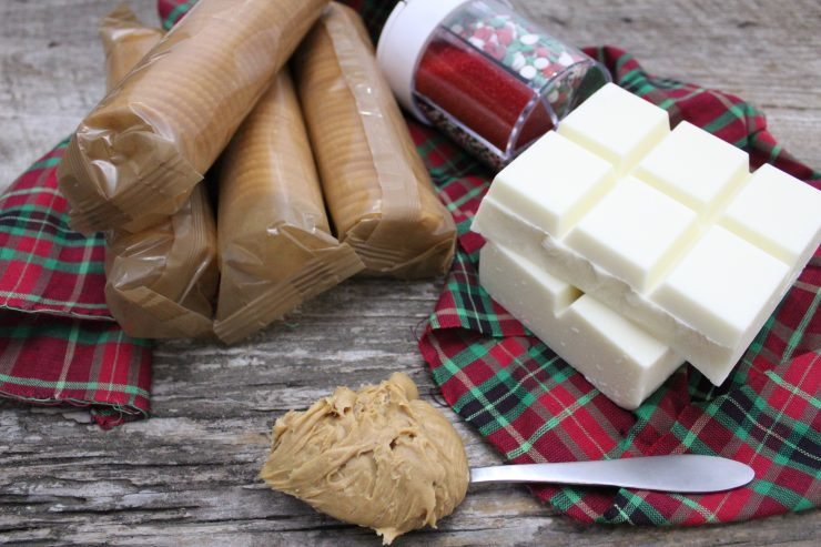 Four packages of Ritz crackers, a container of assorted Christmas sprinkles, two blocks of white chocolate almond bark, and a silver tablespoon of creamy peanut butter is laid out on a wooden back drop with a tartan plaid cloth underneath it all.