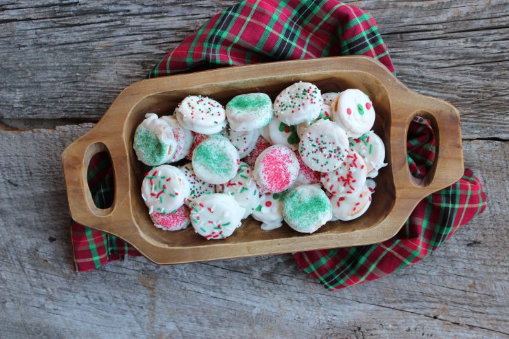 A wooden trencher is sitting in the center of a wooden backdrop and is filled with White Chocolate Ritz Cookies that are covered in festive, Christmas sprinkles of red, white, and green. A red, green, and black tartan cloth is under the trencher.