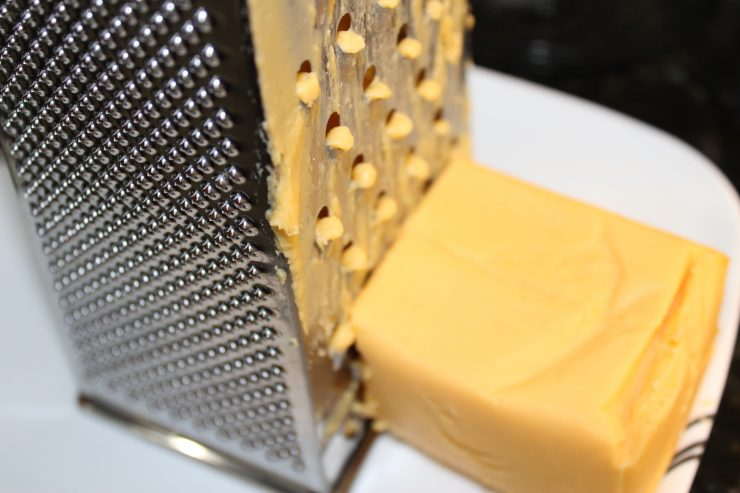 A silver cheese grater sits on a white plate with a block of orange, Velveeta cheese next to it. The block of cheese has been grated on the cheese grater and remnants of the cheese clings to the cheese grater.