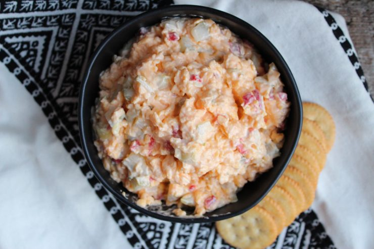 An overhead shot of Pimento Cheese in a black bowl with crackers to the right of the bowl. The bowl is sitting on a black and white towel.