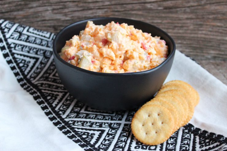 A black bowl of Southern Pimento Cheese sits on a black and white Aztec towel against a wooden backdrop. A pile of Ritz crackers are placed to the right of the bowl.