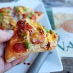 A hand is coming out of the left hand side of the photo and is holding a slice of Naan Bread Breakfast Pizza.