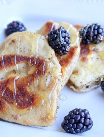 A bright, white plate contains three heart shaped Naan Bread French Toast that has been drizzled with honey and garnished with blackberries.