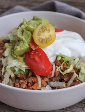 A white bowl filled with ground beef and cauliflower rice and topped with sour cream, guacamole, shredded lettuce, and sliced cherry tomatoes sits on a wooden backdrop with a gold fork beside the bowl and a blue towel visible around the bowl.