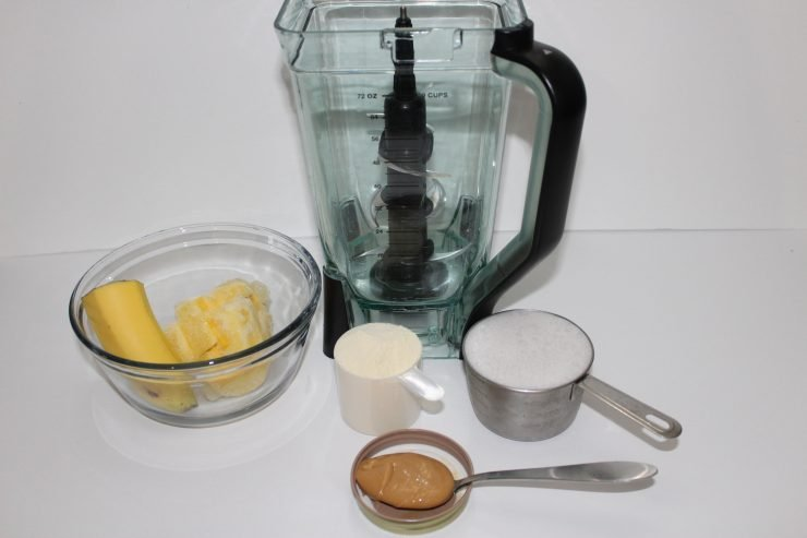 A high powered blender sits against a white backdrop with a clear, glass bowl on the left hand side. The bowl contains frozen pineapple and half of a banana. A silver measuring cup filled with coconut milk is placed in front of the blender and a plastic scoop full of vanilla protein powder is also in front of the blender. A silver tablespoon holding creamy cashew butter is also in front of the blender.