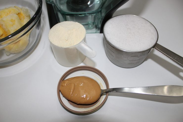 A tablespoon of creamy cashew butter sits on a white backdrop along with a scoop of vanilla protein powder and a cup of coconut milk.