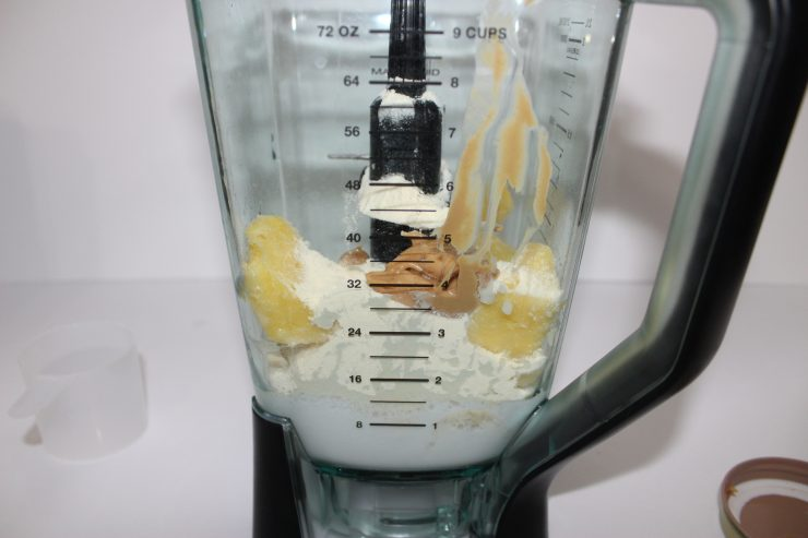 A blender containing banana, pineapple, vanilla protein powder, coconut milk, and cashew butter sits against a white backdrop.