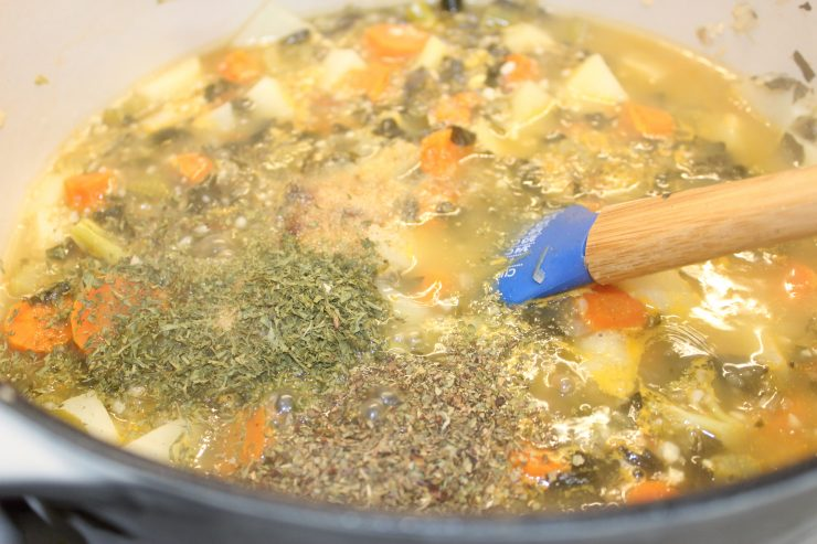 A white Dutch oven filled with carrots, broccoli, celery, potatoes, chicken broth, dried parsley, dried basil, onion powder, garlic powder, ground black pepper, and pink Himalayan salt sits on a stove top with a blue spatula inside.