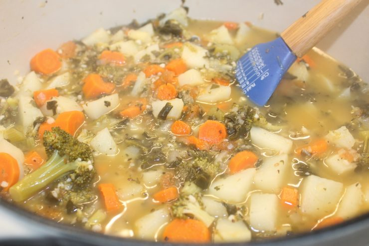 Cooked Cheesy Vegetable Soup sits on a stove top in a white Dutch Oven with a blue spatula inside.