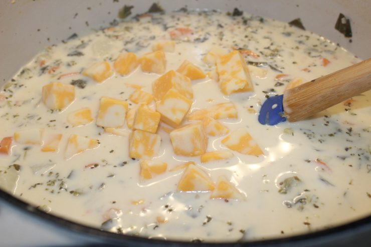 Cheesy Vegetable Soup sits on the stove top with heavy whipping cream added in and cubed American and Colby Jack cheese floating on top. A blue spatula is also resting inside the pot.