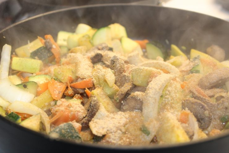 A large, deep, black skillet with portabello mushrooms, sesame oil, minced garlic, sliced green onion, carrot ribbons, and diced zucchini and yellow squash along with sliced white onion inside cooking on a white stove top. Ground garlic and ground white pepper has been added to the skillet.