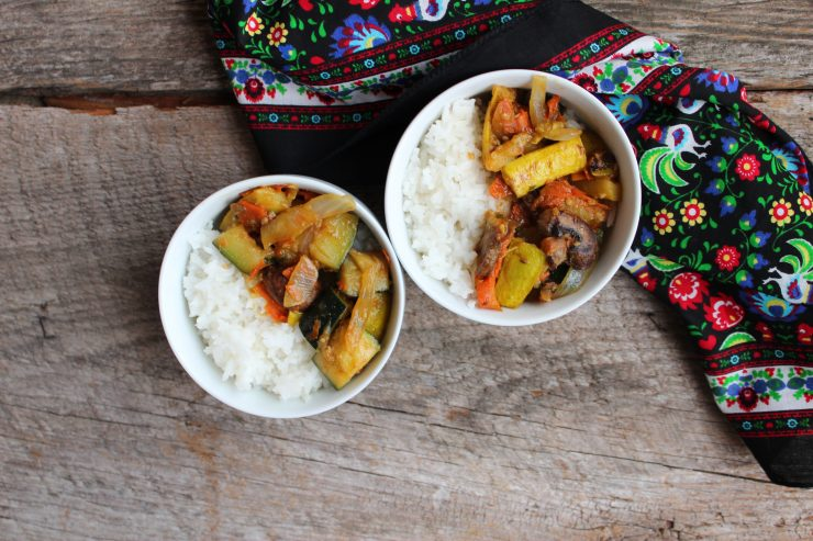 Two white bowls of cooked white rice and Asian Vegetable Stir Fry on a wooden backdrop. A multi colored floral towel is on the right hand side of the bowls.