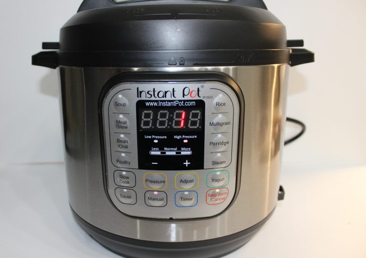 A silver and black Instant Pot DUO electric pressure cooker sits on a white backdrop with the lid locked in place. The digital front screen shows that the pressure cooker is on and set cook on manual, high pressure for one minute.