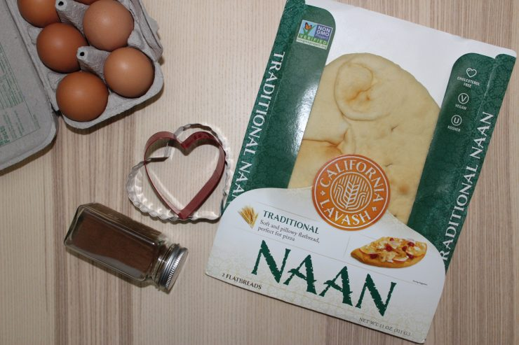 A carton of brown eggs barely shows in the upper left hand corner of the photo with a bottle of ground cinnamon in the middle, alongside red and silver cookie cutters and a package of California Lavash Naan Bread.