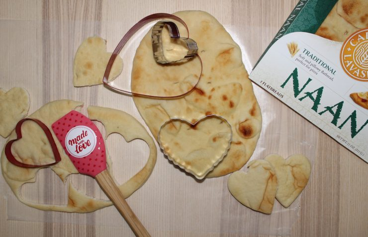 Two sheets of Naan Bread sits in the center of a table, one with heart shapes already cut out of it with heart shaped cookie cutters. A pink and red spatula is also beside the Naan bread and a package of California Lavash Naan Bread peeks out of the right hand side of the frame.