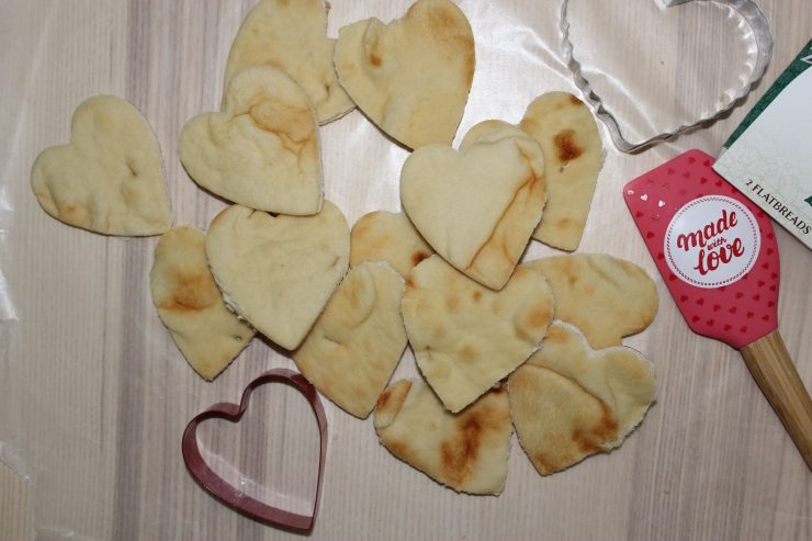 Heart shaped Naan Bread is on the center of a wooden table with a red and silver heart shaped cookie cutter placed beside the heart shaped Naan Bread.