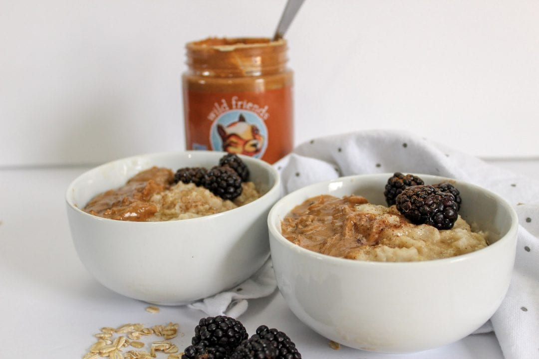 Two white bowls filled with oatmeal and topped with peanut butter, honey, blackberries, and cinnamon. Oats and blackberries are scattered on a white background where the bowls sit and a white and grey polka dot towel is visible behind the bowls. A jar of Wild Friends peanut butter is visible behind the bowls with a silver spoon inside.