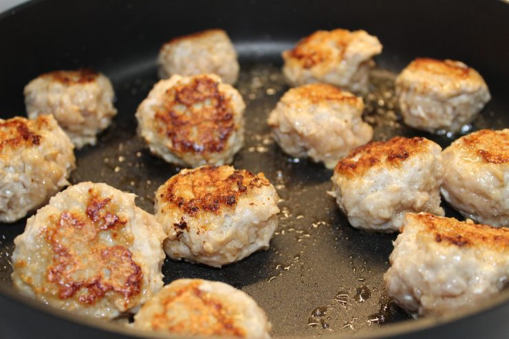 Golf ball sized chicken meatballs sit in a black skillet, browned and cooked.