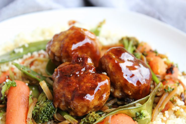 Teriyaki glazed chicken meatballs sit on a bed of cooked stir fry and couscous on a white plate.