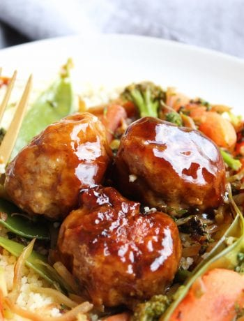 A close up photo of three Paleo Teriyaki Chicken Meatballs on a bed of cooked stir fry and couscous. The food is sitting on a white plate and a gold fork is resting in the plate on the left. A blue towel is in the background.