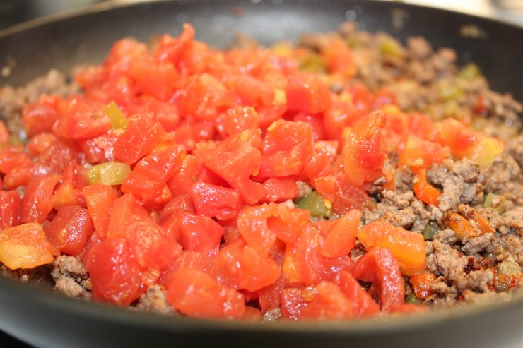 Cooked ground beef in a large black skillet with diced celery, onion, bell pepper, and minced garlic. A can of mild diced tomatoes with green chilies and the liquid has been added to the meat, along with cumin, paprika, salt, and chili powder.