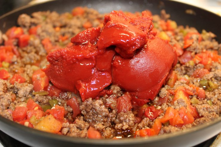 Tomato paste and amber agave nectar has been added to the black skillet containing cooked ground beef, seasonings, and veggies.