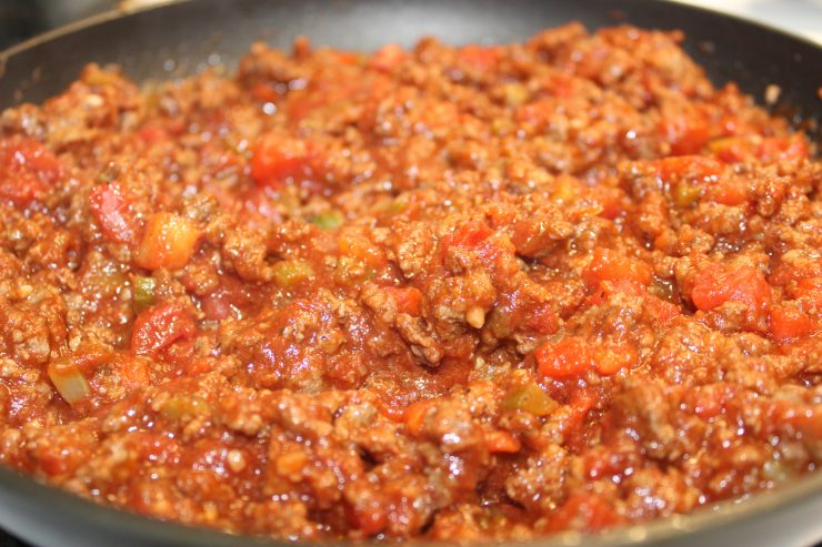Homemade Paleo Sloppy Joe mix sits on a stove in a large black skillet.