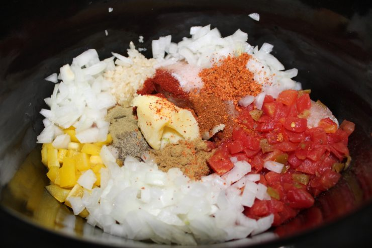 A black slow cooker fills the frame and contains fresh chopped white onion, fresh diced yellow bell pepper, two frozen boneless skinless chicken breasts, ghee, diced tomatoes with green chili's, and spices and seasonings.