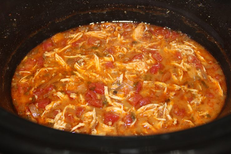 A black slow cooker containing cooked Gluten Free Chicken Tortilla Soup fills the frame. The chicken has been removed and shredded and then stirred back into the Paleo Slow Cooker Chicken Tortilla Soup.