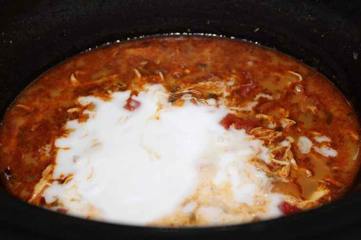A black slow cooker containing cooked Creamy Chicken Tortilla Soup fills the frame. The chicken has been removed and shredded and then stirred back into the Gluten Free Slow Cooker Chicken Tortilla Soup. One can of coconut milk has been added to the contents in the slow cooker but has not been stirred in yet.