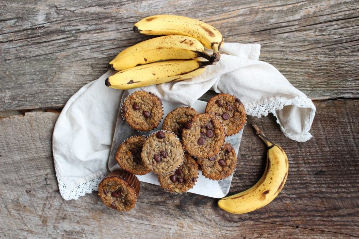 An overhead shot of Gluten Free Banana Chocolate Chip Muffins on a marble cutting board with a few bananas scattered around. Everything sits on a wooden backdrop and a cream towel with white lace edging is under the cutting board.