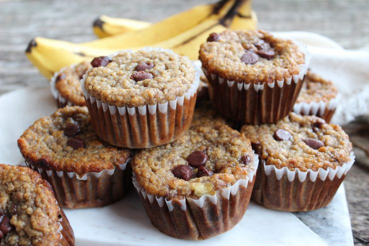 Gluten Free Banana Chocolate Chip Muffins sit piled on a marble cutting board with bananas behind the cutting board. Everything is sitting on a wooden backdrop and a cream towel is visible just behind the bananas.