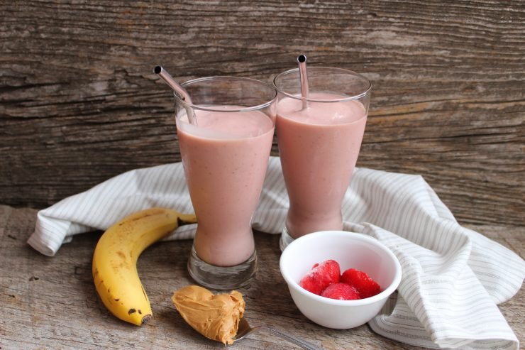 Two clear glasses with stainless steel straws sit against a wooden back drop with a white and grey striped towel around them. A yellow banana is on the left of the glasses and a silver spoon with peanut butter on it is in front of them. A white bowl with three red strawberries sits to the right of the glasses. The glasses are filled with pink, Peanut Butter and Jelly Protein Smoothie.
