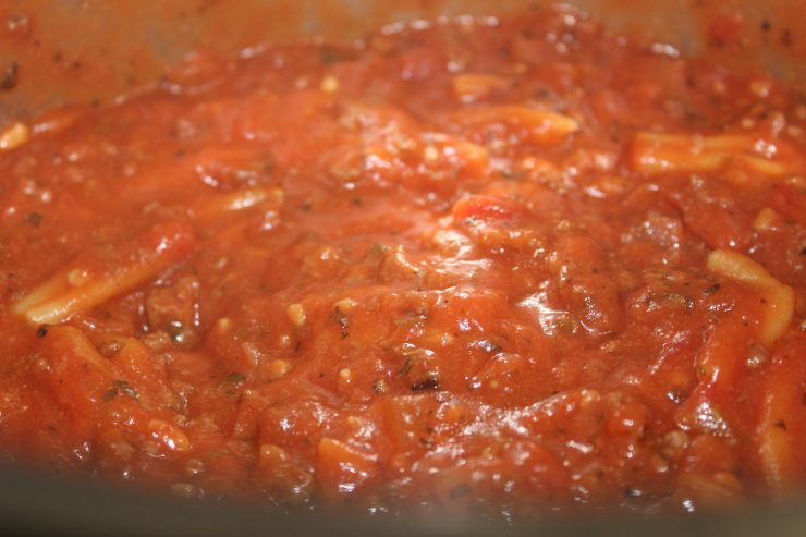 A silver Instant Pot insert filled with cooked, red spaghetti sauce and barely visible cooked chickpea pasta inside.