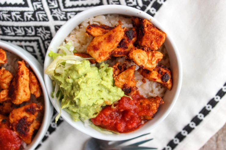 A white bowl filled with pan grilled diced chicken, guacamole, shredded lettuce, red salsa, and Cilantro Lime Rice is sitting on a black and white towel.