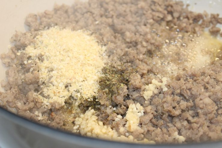 A white dutch oven sits on a stove top with cooked and crumbled breakfast sausage in it. Dried minced onion, salt, Italian seasoning, dried red pepper flakes, and fresh minced garlic has been added to the sausage for seasoning.