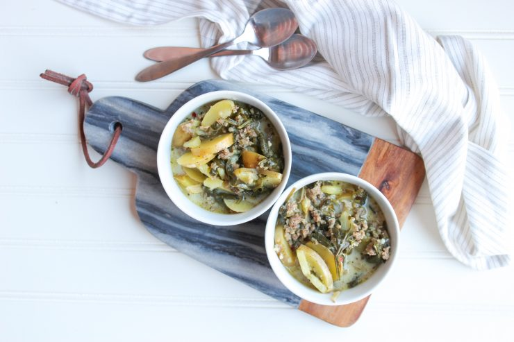 Two white bowls filled with Dairy Free Zuppa Toscana Soup sit on a blue marble and wood cutting board. The cutting board has been placed on a white background. A white and grey striped towel is behind the cutting board with two silver spoons resting on it.