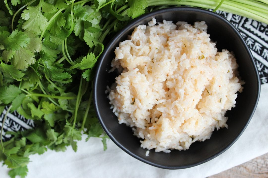 A black bowl filled with Cilantro Lime Rice sits on a black and white towel with a bunch of green, leafy, Cilantro around the bowl.