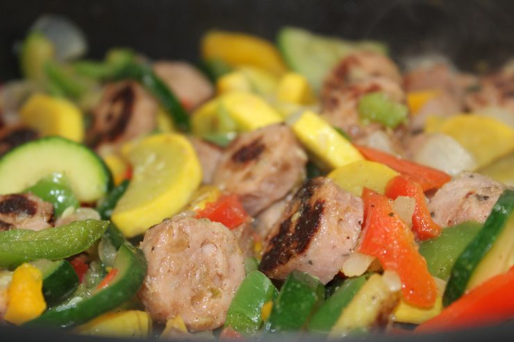 A large, deep black skillet filled with sliced green zucchini, yellow squash, and browned chicken apple sausage sits on a stove top cooking. Cooked and seasoned yellow, red, and green bell peppers and white onions have been added to the skillet.