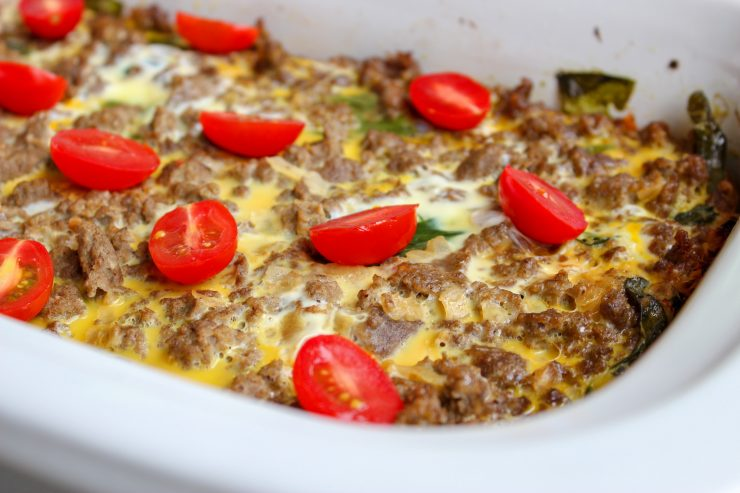 Close up photo of the Slow Cooker Breakfast Casserole in a white, 9x13 Crockpot casserole dish. The Breakfast Casserole is topped with sliced, red cherry tomatoes.