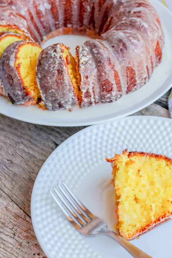 Lemon pound cake on a white plate with three slices cut in the front of the cake. The cake has a white, gray, and yellow striped towel around the plate and is sitting on a barn wood board back drop.