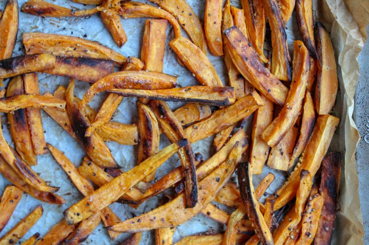 Crispy Baked Sweet Potato Fries are scattered on a browned parchment paper that has been placed on a silver sheet pan.