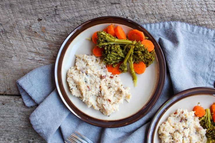 A cream plate with brown edging is visible on a wooden backdrop. The plate has a blue towel underneath and another identical plate can just be seen in the bottom right of the photo. The plate contains a helping of Instant Pot Cheesy Chicken and Rice along with a side of steamed broccoli florets and sliced carrots.