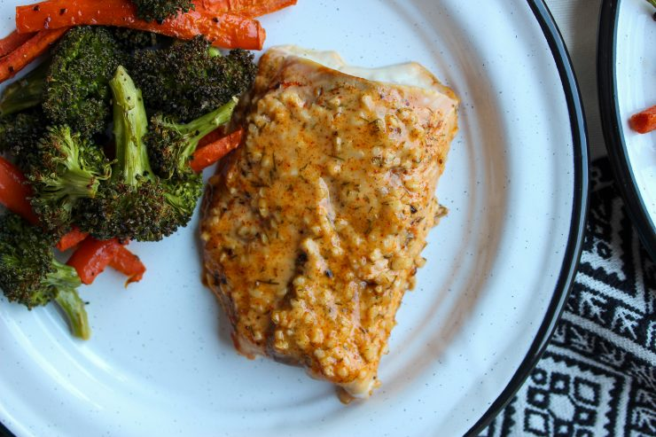 A juicy, golden, baked salmon filet topped with Creamy Garlic Sauce is resting on a white plate with black edging. The salmon is served with a side of roasted carrots sticks and broccoli florets. A white and black Aztec printed towel can just barely visible underneath the plate.
