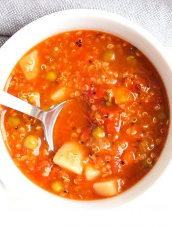 A bright, white bowl filled with Slow Cooker Vegetable Quinoa Soup sits on a white backdrop with a blue towel behind it and a barely visible bowl of vegetable soup beside it. A silver spoon has been placed in the bowl.