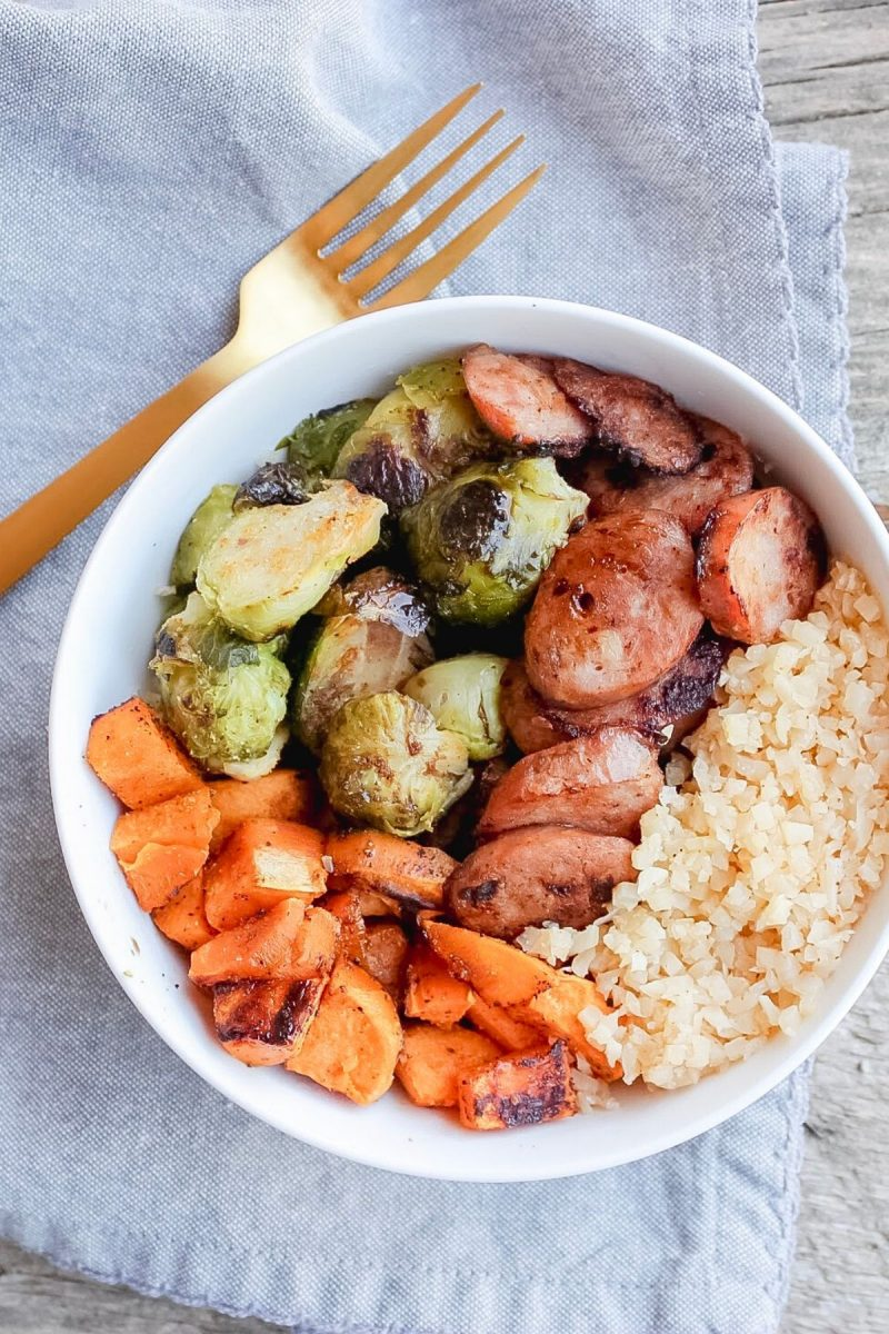 A white bowl containing the key ingredients for these Low Carb Buddha Bowls, such as roasted sweet potatoes, Brussels sprouts, chicken sausage, and riced cauliflower.