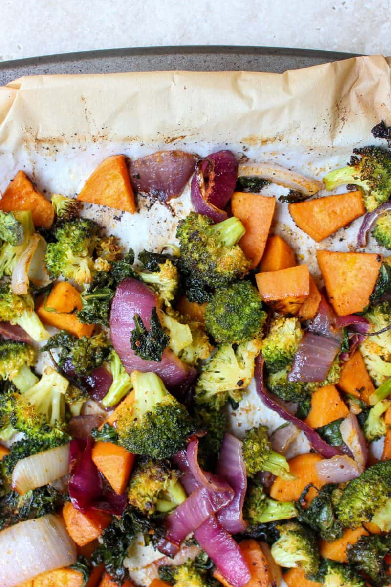 a sheet pan filled with savory roasted vegetables for vegan sweet potato buddha bowl